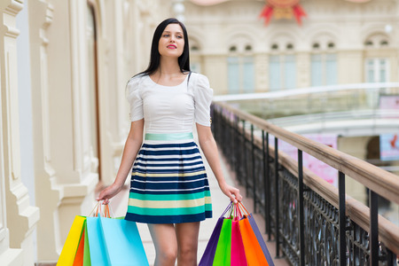 spendthrift: Beautiful smiling young woman with the colourful shopping bags from the fancy shops. Stock Photo