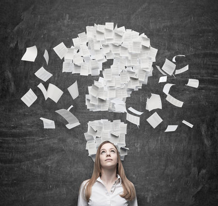 interrogative: Business woman is thinking about the question mark which consists of the contract pages. Dark background. Stock Photo