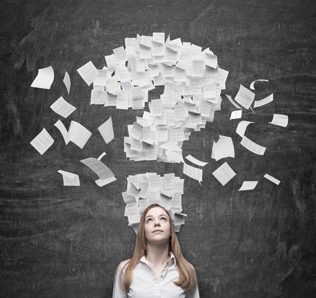 interrogative: Mujer de negocios que piensa en el signo de interrogaci�n que consiste en las p�ginas del contrato. Fondo oscuro.