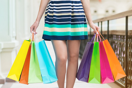 spendthrift: A woman with a lot of colourful shopping bags.