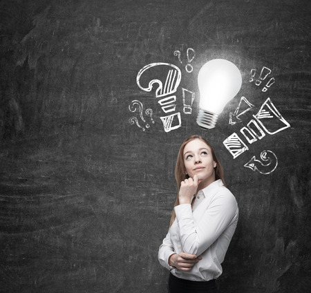 originality: Beautiful business woman is thinking about optimisation measures for business. turned lightbulb and question and exclamation marks Stock Photo