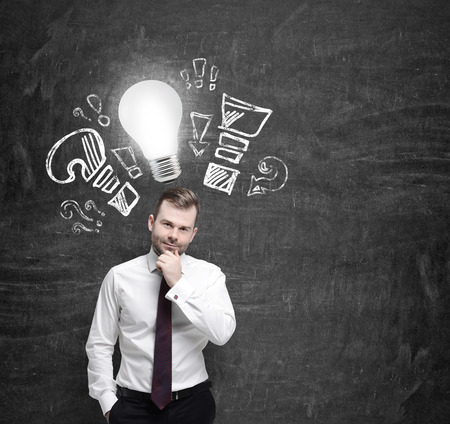 Confident businessman is thinking about optimisation measures for business. Turned lightbulb and question and exclamation marks