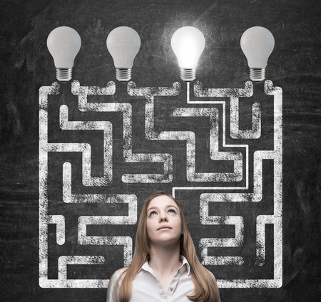 Beautiful woman is looking for the way how to solve the maze and reach the right light bulb as a concept of the perfect business solution.
