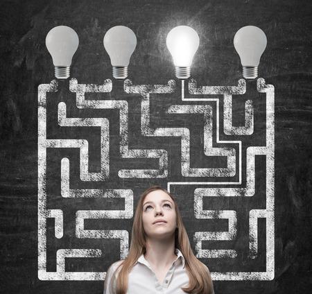 mujeres pensando: Hermosa mujer est� buscando la manera de c�mo resolver el laberinto y llegar a la bombilla derecha como un concepto de la soluci�n de negocio perfecto. Foto de archivo