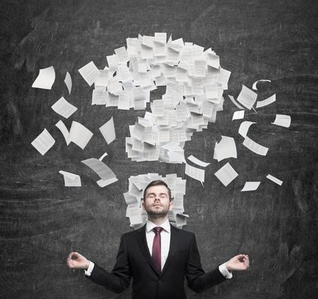 interrogativa: Mediar empresario est� pensando en el signo de interrogaci�n que consiste en las p�ginas del contrato. Fondo oscuro. Foto de archivo
