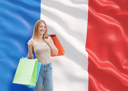 french fancy: A happy young woman with the colourful shopping bags from the fancy shops. French flag background.