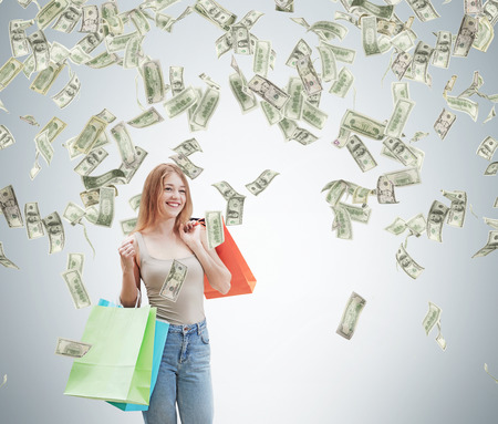 spendthrift: A happy young woman with the colourful shopping bags from the fancy shops. Dollar notes are falling down from the ceiling. Concrete background. Stock Photo