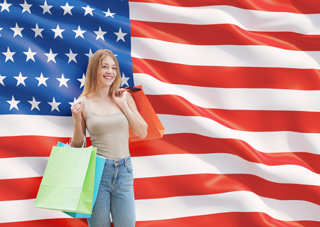 A happy young woman with the colourful shopping bags from the fancy shops. US flag background. Stock Photo