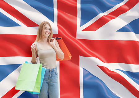 great britain flag: A happy young woman with the colourful shopping bags from the fancy shops. Great Britain flag background.
