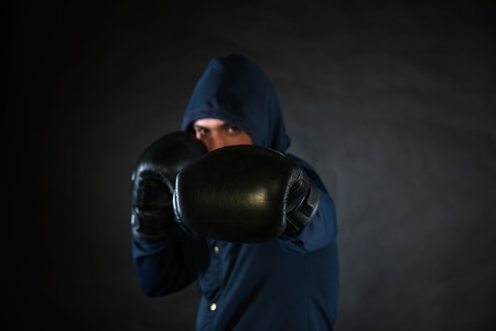 pugilist: Hooded man in a fighting stance with black boxer gloves. Stock Photo