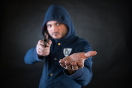 heist: A person in a hoodie is aiming and holding the other hand. A concept of the robbery.