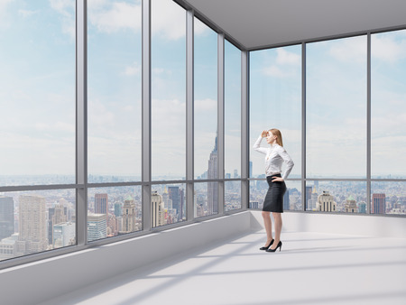 moving office: Full length business lady looks at the financial district in New York city. Panoramic contemporary office.