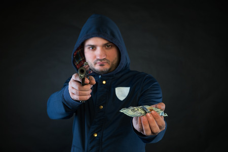 stickup: A person in a hoodie is aiming and holding the other hand with the dollar note. A concept of the robbery.