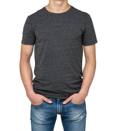 midriff: Man wearing dark grey t-shirt isolated on white background. Hands in the pockets.