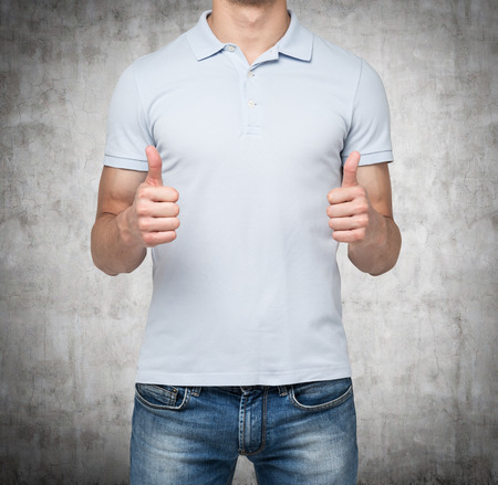 ok sign: A person with thumbs up. Concrete background. Stock Photo