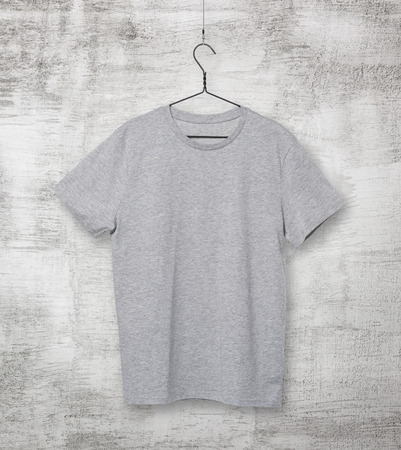 tee shirt: Close-up of the grey t-shirt on the clothes hanger. Concrete background. Stock Photo