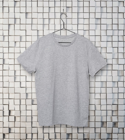collarless: Close-up of the grey t-shirt on the clothes hanger. Mosaic background.