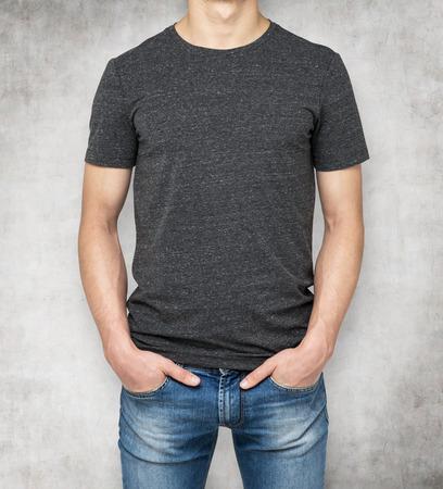 the shirt: El hombre que llevaba la camiseta de color gris oscuro, fondo de hormig�n. Las manos en los bolsillos.