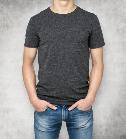 men body: Man wearing dark grey t-shirt, concrete background. Hands in the pockets.