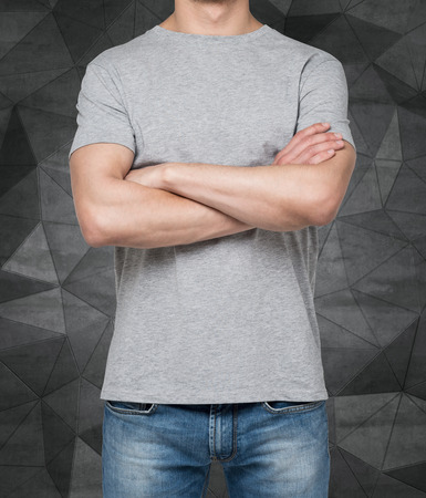 midriff: Man wearing grey t-shirt with crossed hands, Isolated on dark concrete background.
