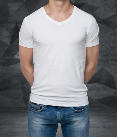 midriff: Close up of the body view of the man in a white t-shirt. Hands are crossed behind the back. Contemporary office background. Stock Photo