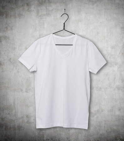 collarless: Close-up of the white t-shirt on the clothes hanger. Concrete background.