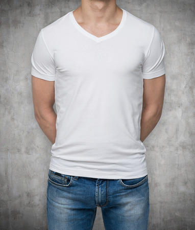 denim fabric: Close up of the body view of the man in a white t-shirt. Hands are crossed behind the back. Concrete background.