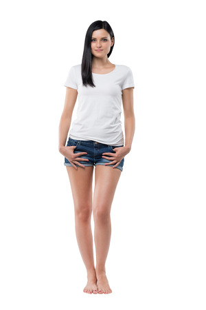 woman barefoot: Full length of a brunette woman in a white t-shirt and denim shorts. Isolated. Stock Photo