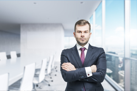CEO with crossed hands in the modern conference room. A concept of successful business. Panoramic office, New York City view. Stock Photo