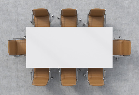 Vue d'en haut d'une salle de conférence. Une table rectangulaire blanc et huit chaises en cuir marron autour.