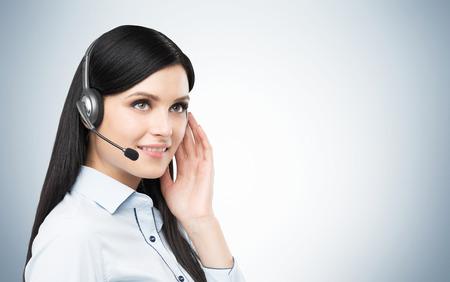 recepcionista: Retrato de la sonrisa alegre operador de soporte telef�nico en el auricular. Estudio fondo azul.