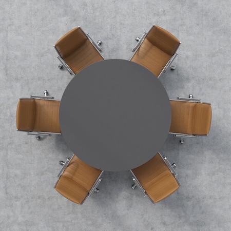 Bovenaanzicht van een conferentieruimte. Een donkere grijze ronde tafel en zes bruine lederen stoelen rond. Stockfoto
