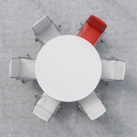 Bovenaanzicht van een conferentieruimte. Een witte ronde tafel en een rode en vijf witte stoelen.