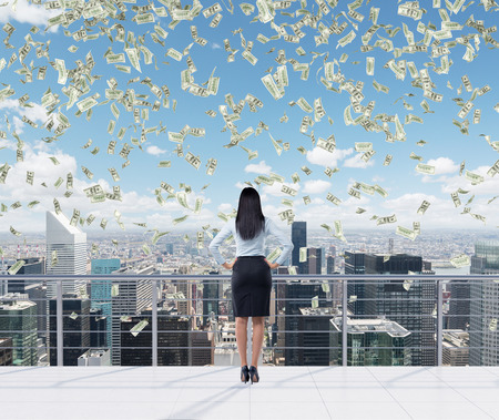 financial cash: Rear view of the full length brunette woman who stands on the roof terrace in New York city. Falling dollar notes are falling down from the sky. Stock Photo