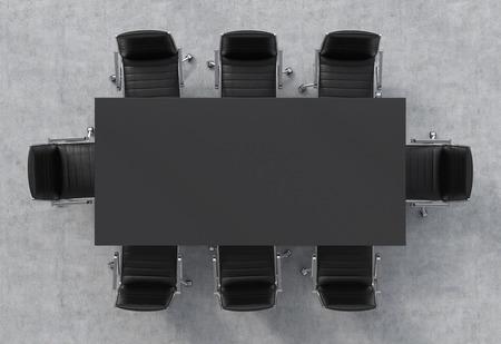 Bovenaanzicht van een conferentieruimte. Een zwarte rechthoekige tafel en acht zwarte lederen stoelen rond.