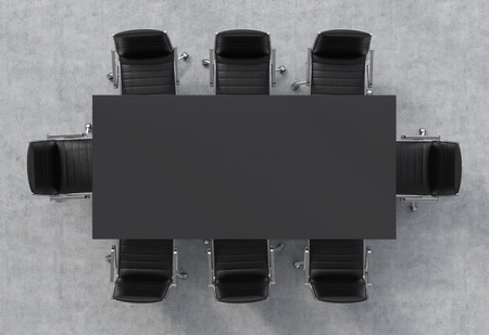 Top view of a conference room. A black rectangular table and eight black leather chairs around. Stock Photo
