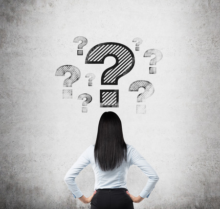 Rear view of the brunette who looks on the drawn question marks. Concrete background.