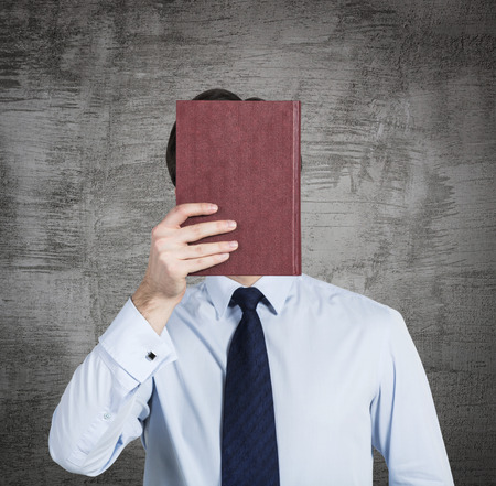 obscurity: A person holds a red book in front of the head. Concrete background.
