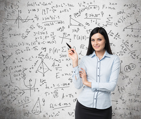 math: Portrait of smiling woman who points out complicated math calculations. Math formulas are written on the concrete wall.