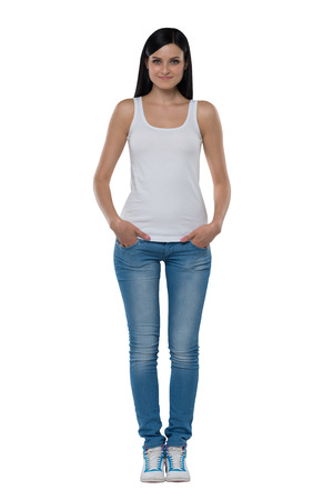 Full length of a brunette woman in a white tank top and jeans. Isolated. Stock Photo
