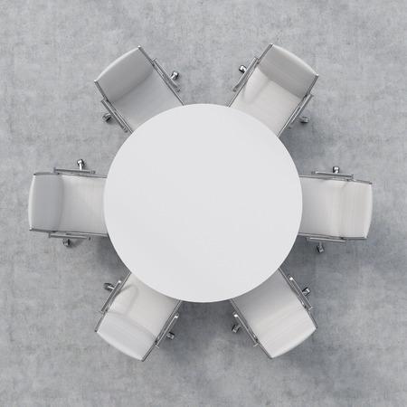 Vista de cima de uma sala de conferências. Uma mesa-redonda branca e seis cadeiras ao redor. Imagens