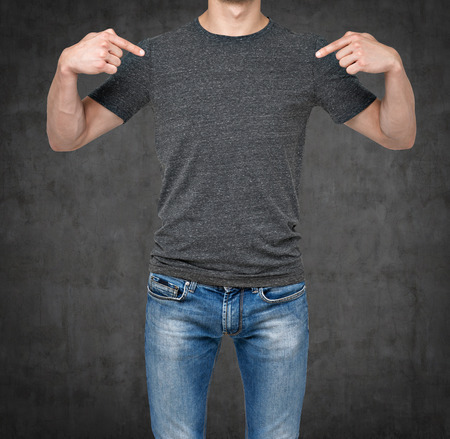 endorsing: Close-up of a man pointing his fingers on a blank grey t-shirt. Dark concrete background.