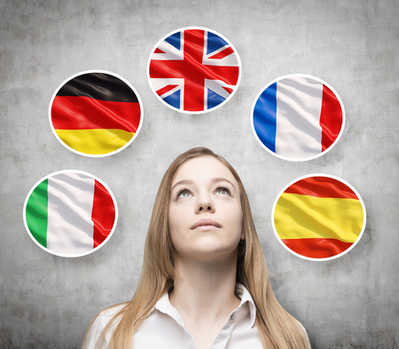 Beautiful lady is surrounded by bubbles with european countries' flags (Italian, German, Great Britain, French, Spanish). Learning of foreign languages concept. Concrete background. Imagens