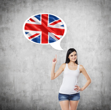 great britain flag: Brunette lady is pointing out the thought bubble with Great Britain flag inside. Concrete background. Stock Photo