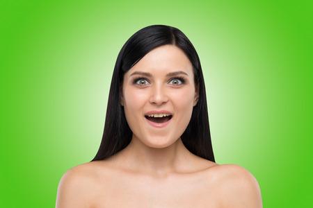 agape: Portrait of an astonished brunette girl. Green background.