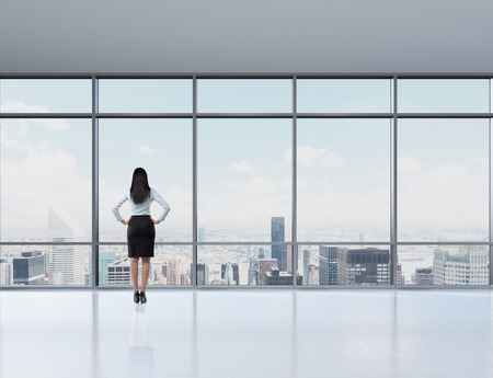 office window view: Rear view of brunette woman in the office who looks through the window. New York panoramic office. A concept of a successful woman in a business. Stock Photo