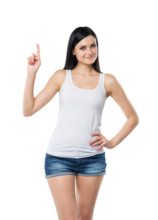 new idea: Close up of a brunette lady in a tank top and denims who points her finger up. A concept of a new idea. Isolated.