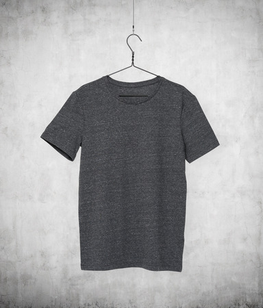 Close up of a grey t-shirt on cloth hanger. Concrete background. Stock Photo