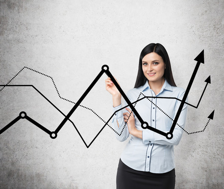 representations: Brunette business lady presents a line graphs, which symbolise fluctuation of the business process. Concrete background.