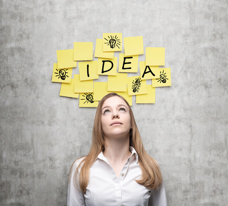 Young business lady is looking for new business ideas. Yellow stickers with the word ' idea' and sketches of ' light bulbs ' are hanged on the concrete wall.